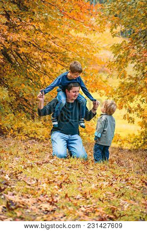 Father Having Fun With Kids In The Autumn Park