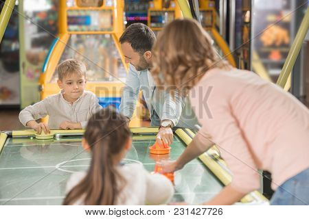Happy Family With Two Children Playing Air Hockey Together In Game Center
