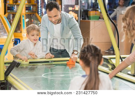 Cropped Shot Of Family With Two Kids Playing Air Hockey Together In Game Center