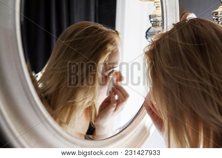 Woman using a cotton pad to remove her makeup in the bathroom at night.