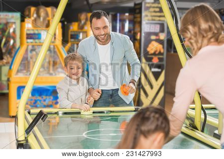 Happy Family With Two Kids Playing Air Hockey Together In Entertainment Center