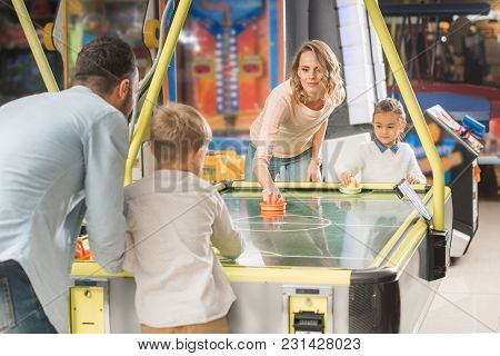 Happy Family Playing Air Hockey Together In Entertainment Center