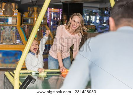 Selective Focus Of Parents With Happy Little Daughter Playing Air Hockey In Game Center