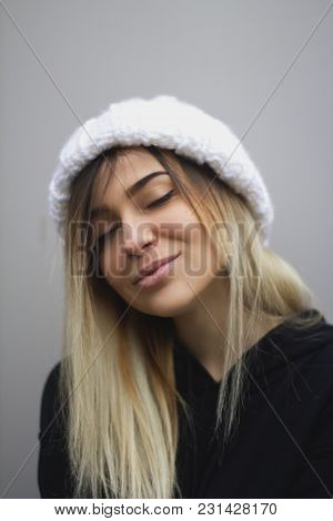 Blonde Girl With Big Eyes And Plump Lips Against A Light Gray Background. Woman In A Volumetric Warm