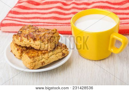 Shortbread Cookies With Peanuts In Saucer, Cup Of Milk, Red Napkin On Wooden Table