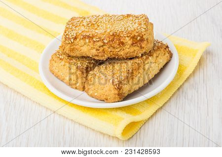 Shortbread Cookies With Sesame In Saucer On Yellow Napkin On Wooden Table