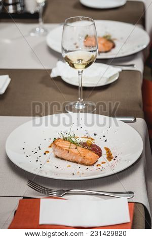 Delicious Salmon In A Restaurant. Small Portion On A White Plate. Food And Wine Tasting