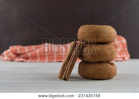 Cinnamon Sticks Leaning Against Donuts In Stack