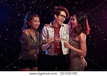 Group Of Cheerful Asian Friends Clinking Champagne Flutes Together While Celebrating New Year At Nig