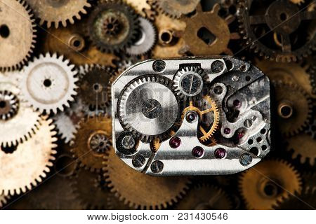 Vintage Clock Mechanism Close-up. Aged Hand Watches Parts On Bronze Gears Background