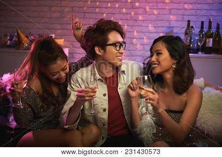 Hanging Out With Friend At Night Club: Two Pretty Asian Women And One Handsome Man Sitting On Sofa W