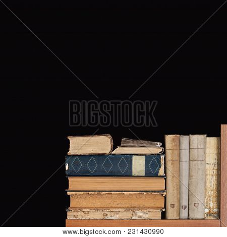 Book Shelf On Black Background. Rare Vintage Library Books Collection, Antique Textured Covers. Aged