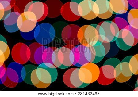 Circles Of Irregular Shapes Of Different Colors On A Black Background. Abstract Lights.
