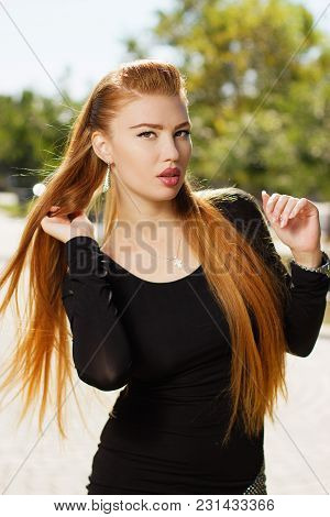 Portrait Of Beautiful Sexy Urban Girl Walking In City Park. Portrait Of A Young Gorgeous Redhead Gir