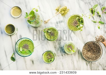 Matcha Green Vegan Smoothie With Chia Seeds And Fresh Mint In Glasses And Bottles Over Marble Backgr