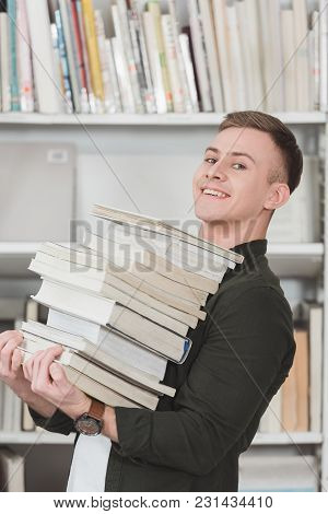 Side View Of Smiling Student Holding Stack Of Books And Looking At Camera