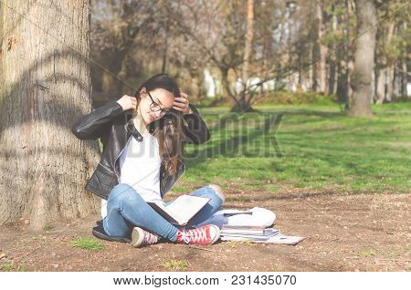 Beautiful Young School Or College Girl With Long Hair, Glasses And Black Leather Jacket Sitting On T