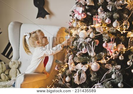 Baby Playing With Decorations On A Christmas Tree.