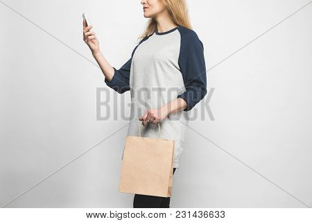 Cropped Shot Of Woman In Stylish Long Sleeve On White With Shopping Bag And Smartphone