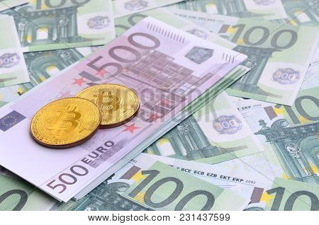 Golden Physical Bitcoins Is Lies On A Set Of Green Monetary Denominations Of 100 Euros. A Lot Of Mon