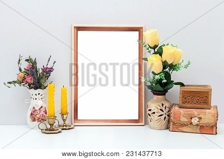 A4 Wooden Frame Mockup With Yellow Flowers, Candles And Boxes. Portrait Orientation.