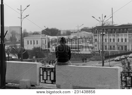 A Man In A Black Jacket And Hood Sitting On A Parapet Alone And Looking At The City