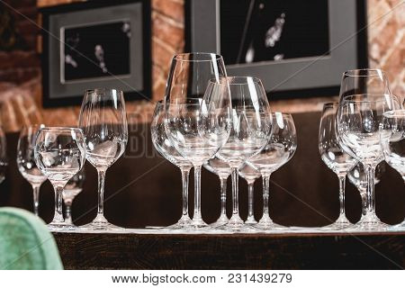 Empty Glasses Of Different Shapes Served In A Restaurant For A Wine Tasting. Sommelier At Wine Tasti