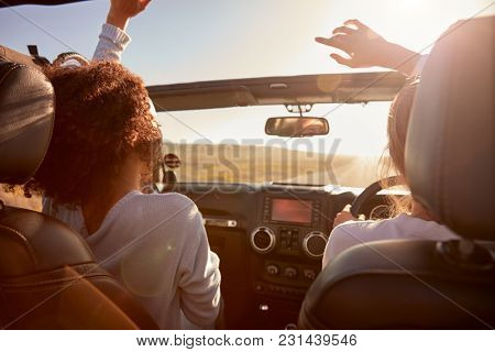 Young white woman looking to camera from open window of car