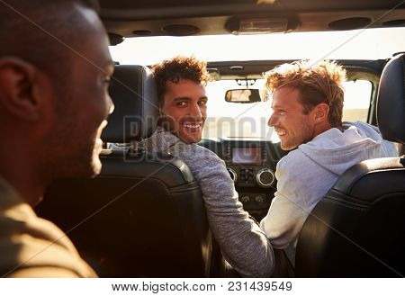 Three young adult men driving in a car with sunroof open