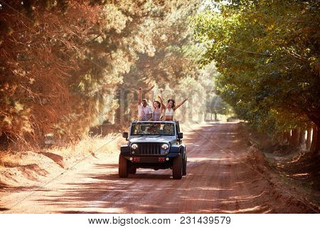 Friends having fun driving in an open top car
