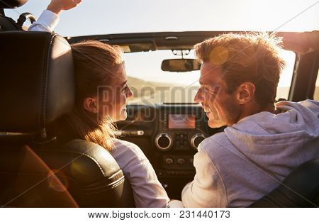Couple drive looking at each other, rear passenger POV