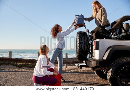 Three young adult girlfriends unloading backpacks from a car