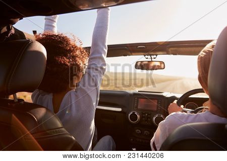 Two young female friends driving a car in the sun, side view