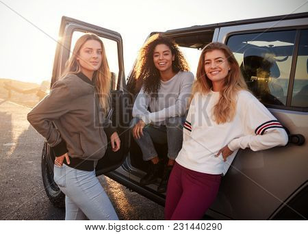 Three female friends on road trip looking at camera from car