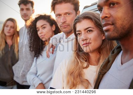 Young adult friends on a road trip standing by car, close up