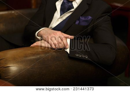 Hands Of The Man Lie On The Back Of The Chair, He Himself In A Dark Suit With A Purple Handkerchief,