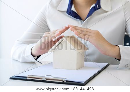 Insurance And Care Protection Of House Concept, Woman With Protective Gesture Of Small Home Model.