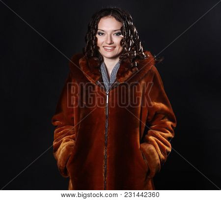 Portrait Of Beautiful Young Woman In Red Coat With Evening Makeup.isolated On A Black Background.