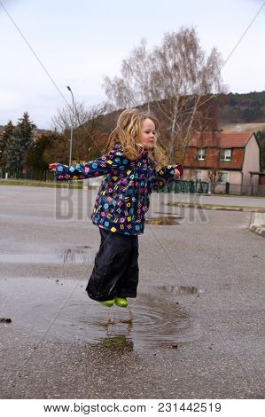Little Blond Girl Jumping Fun In A Puddle