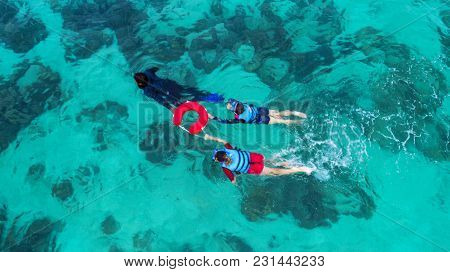 Background Blurred People Swimming In The Sea. Aerial View, Top View. The Color Of The Water And Bea