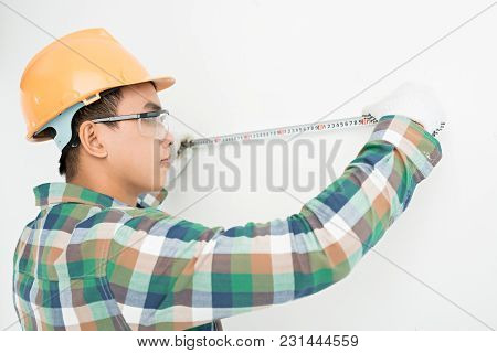 Young Asian Man In Helmet Measuring Wall