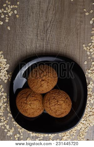 Three Oatmeal Cookies Lie On A Black Plate, Beside Scattered Oatmeal, There Is A Place Under The Tex