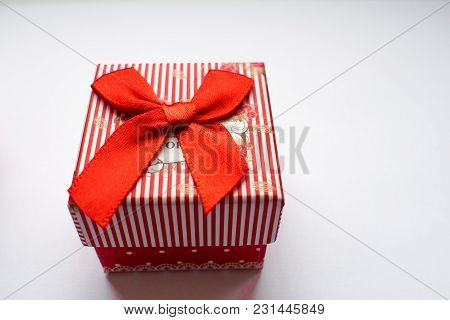 Red, Striped, Small Gift Box On White Paper. Closed. It Creates The Impression Of Intrigue And Surpr
