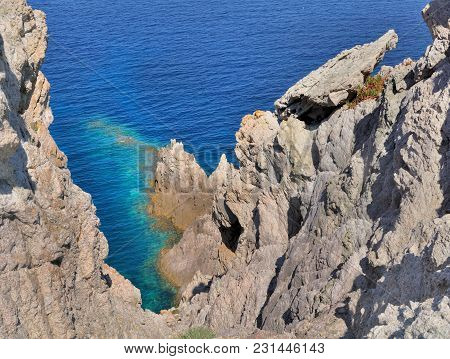 Steep Cliff In Front Of A Blue Sea In Island Of Corsica