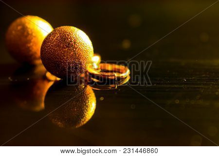 Gold And Yellow Shiny Ball Earrings, Reflected On A Dark Glossy Background. Round With Lock, Close-u
