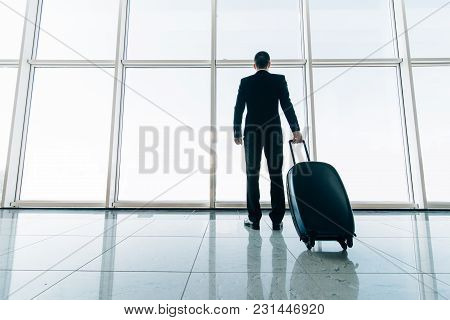 Rear Of Businessman And Suitcase In The Airport Waiting For Flight. Travel Concept, Traveler Suitcas