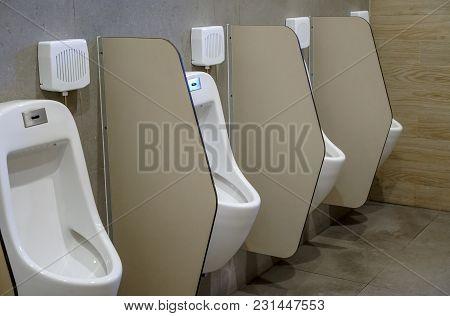 Row Of Outdoor Urinals Men In Public Toilet. Closeup White Urinals In Men's Bathroom.