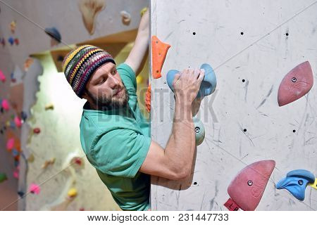 Climber Bouldering In A Sports Hall - Holding On To The Handle Of An Artificial Rock Wall