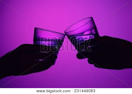 Two Wine Stuffed Glasses And Female And Male Hands At Studio. Vivid Bright Colored Lighting. Trendy