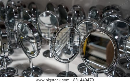 Many Silver Cosmetic Mirrors With Round Frame And Single Stand On White Metal Shelf.